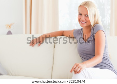 Gorgeous woman sitting on a sofa in her living room