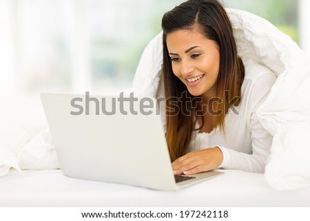 gorgeous woman using laptop computer while lying on her bed - stock photo