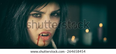 Gorgeous woman vampire angry with blood - stock photo