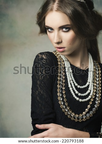 gorgeous woman wearing like a antique dame in charming pose with vintage hair-style and very precious jewellery  - stock photo