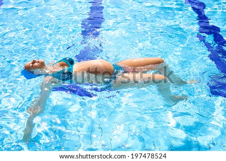 Gorgeous woman with big belly in the water - stock photo