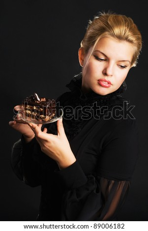 Gorgeous woman with chocolate cake against black