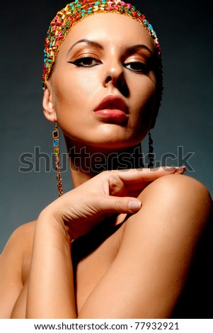 Gorgeous woman with exotic accessories posing on black background