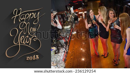 Gorgeous women having cocktails together against classy new year greeting - stock photo