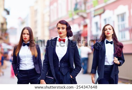 gorgeous women in black walking the city street - stock photo
