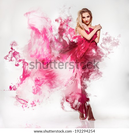 Gorgeous young adult blonde in pink dress with smoke on grey background - stock photo