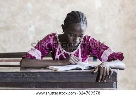 Gorgeous young beautiful African girl sitting in classroom reading a book. Education symbol for Africa. Single person studying learning her lesson. Reading symbol. - stock photo