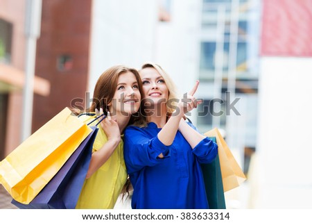 Gorgeous young blond with beautiful brunette pointing at showcase of clothing store. - stock photo