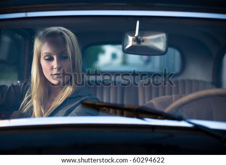 Gorgeous young blonde posing with black vintage car. - stock photo