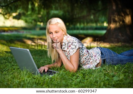 Gorgeous young blonde using laptop mobile net outdoors.
