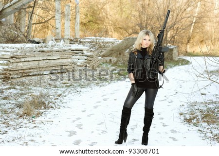Gorgeous young blonde with a gun outdoors