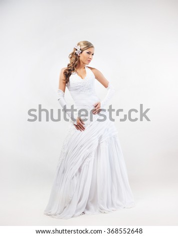 Gorgeous, young bride posing in wedding dress over grey background. - stock photo