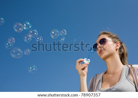 Gorgeous young brunette girl blowing bubbles in to the sky.