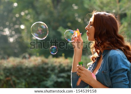 Gorgeous young brunette girl blowing soap bubbles in sunlit park - stock photo