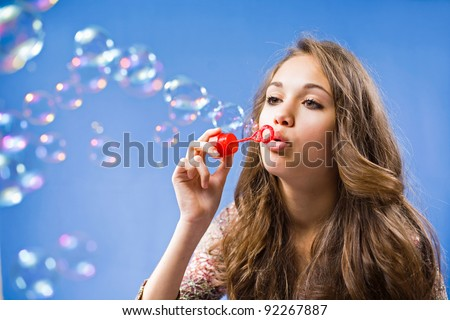 Gorgeous young brunette girl blowing soap bubbles on blue background. - stock photo