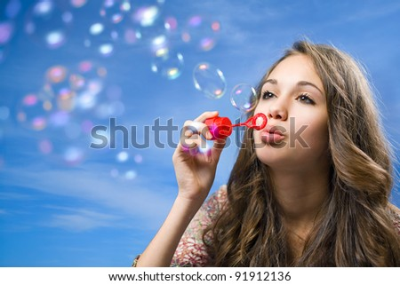 Gorgeous young brunette girl blowing soap bubbles on blue sky. - stock photo