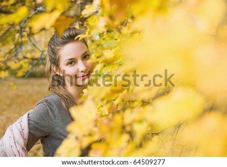 Gorgeous young brunette having fun in autumn park.