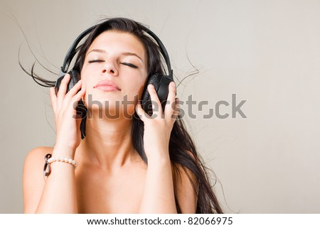 Gorgeous  young brunette immersed in music wearing headphones, with eyes closed