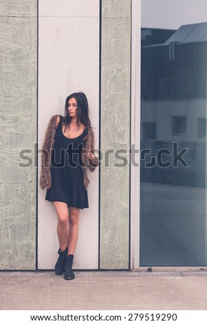 Gorgeous young brunette in black dress posing in an urban context - stock photo