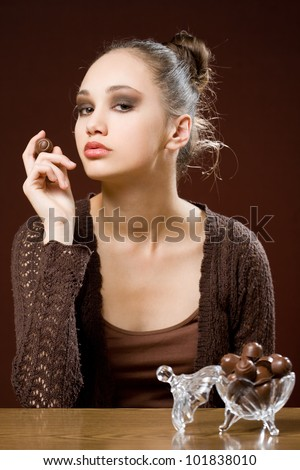 Gorgeous young brunette loving tasty sweet chocolate. - stock photo