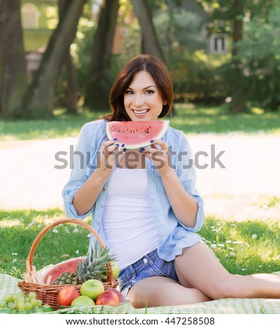 Gorgeous, young brunette sitting on a mat in the park and eating watermelon.