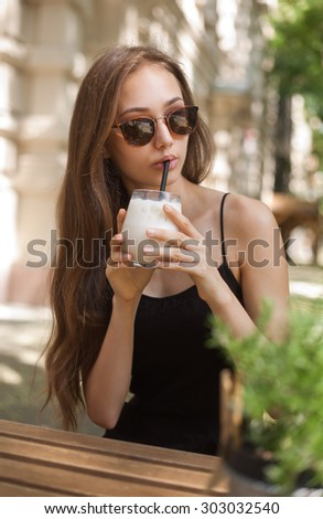 Gorgeous young brunette woman having ice coffee refreshment. - stock photo