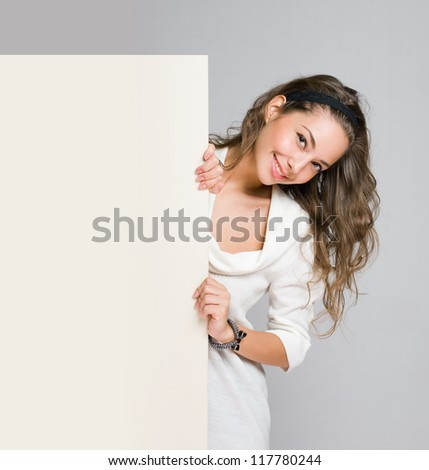 Gorgeous young brunette woman holding blank white billboard. - stock photo