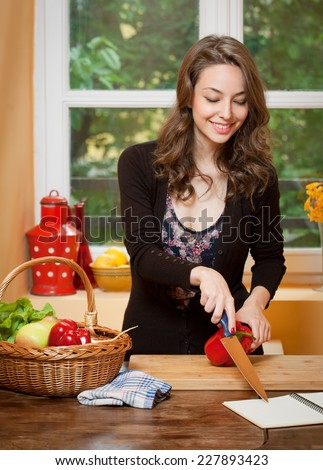 Gorgeous young brunette woman in the kitchen with basket full of healthy food.