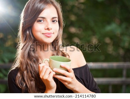 Gorgeous young brunette woman with a green cup. - stock photo