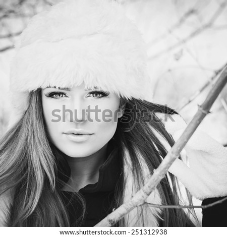 Gorgeous young Caucasian blonde woman in white fur hat and gloves posing outdoors in winter. Black and white, retouched, square image format, matte filter. - stock photo