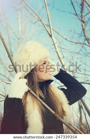 Gorgeous young Caucasian blonde woman with white fur hat, black coat and white gloves in park in winter. Matte filter, vertical, retouched. - stock photo