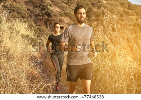 Gorgeous young couple running a mountain path in full sun light with mountain behind them while wearing black and grey