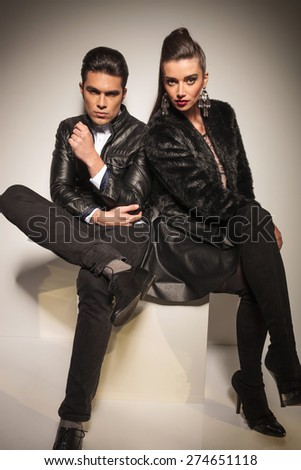 Gorgeous young fashion woman sitting on a white table next to her boyfriend, both looking at the camera.