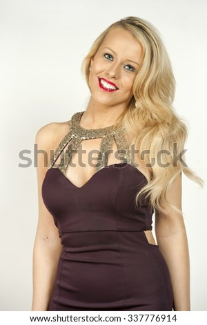 Gorgeous young female blonde with wavy hair in a studio setting while wearing a purple elegant dress on a white background.
