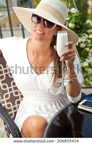 Gorgeous young happy woman in straw hat holding cocktail on a summer day - stock photo