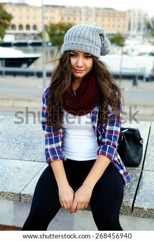 Gorgeous young hipster girl sitting on a bench and looking at the camera, lovely attractive young woman sitting outside - stock photo