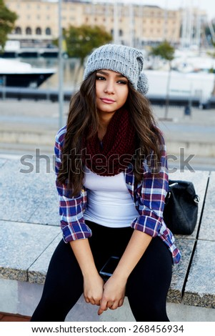 Gorgeous young hipster girl sitting on a bench and looking away, lovely attractive young woman sitting outside - stock photo