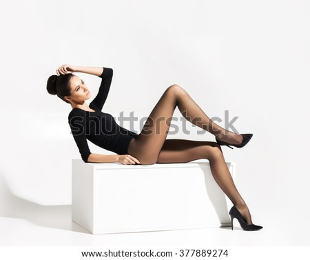 Gorgeous, young lady in alluring hosiery and heels lying on a white cube over isolated background. - stock photo
