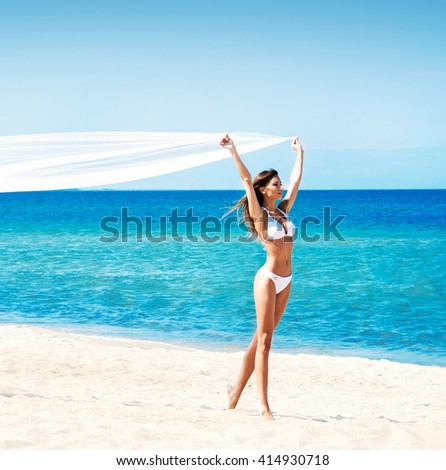 Gorgeous, young lady with slim body and hot legs wearing white alluring swimwear walking along the seacoast with blowing silk blanket. - stock photo
