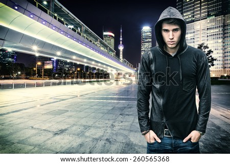 Gorgeous Young Man in Trendy Hooded Shirt Standing at the City Street While Looking at the Camera. - stock photo