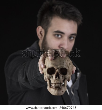 Gorgeous Young Man Wearing Black Jacket Shirt Holding Skull While Looking at the Camera. Isolated on Black Background. - stock photo