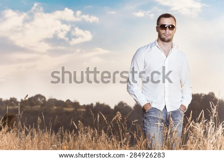 Gorgeous young man with sunglasses posing against sky, outdoors. Copy space. Handsome guy