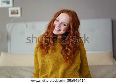 Gorgeous young redhead woman sitting on her bed looking at the camera with a warm friendly smile - stock photo