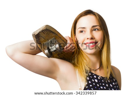 Gorgeous young skateboarding beauty holding old-fashioned wooden skater deck on white background. Retro sports