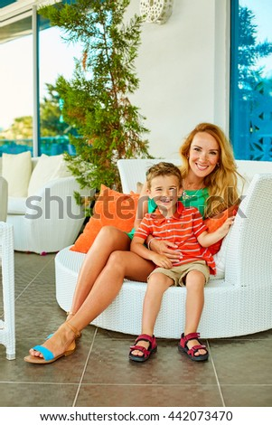 Gorgeous young smiling woman in green dress sitting with little boy in white chair  - stock photo