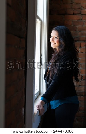 Gorgeous young stylish woman with long dark hair and dark eyes posing in urban loft