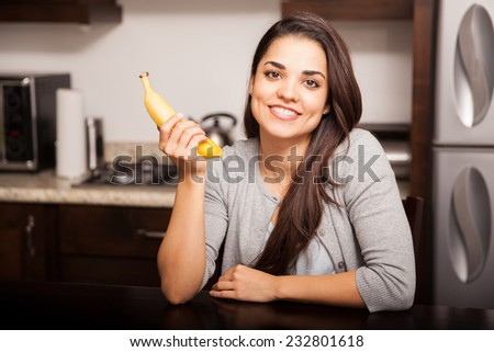 Gorgeous young woman about to eat a banana at home and smiling - stock photo