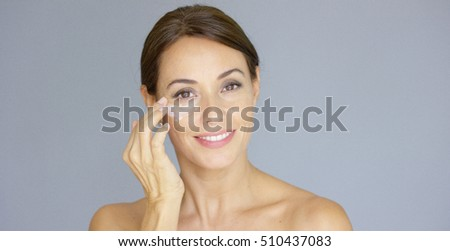 Gorgeous young woman applying face cream