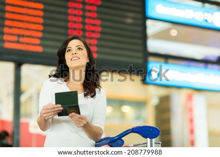 gorgeous young woman checking flight information at airport - stock photo