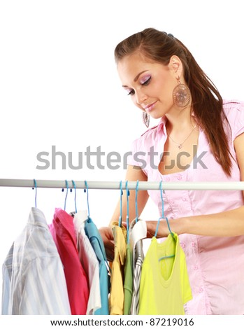 Gorgeous young woman chosing clothes  in store isolated